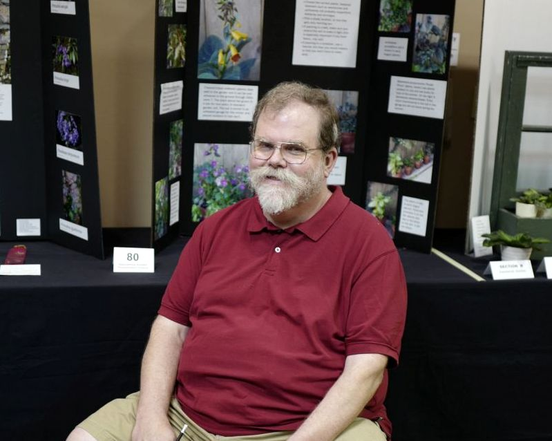 Ray Ruger, Packet co-Chair, in front of the Educational Division exhibits